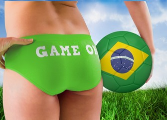 Composite image of fit girl holding brasil ball