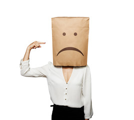 depressed woman pointing at paper bag