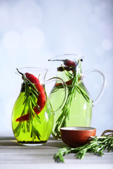 Essential Oil with rosemary in glass jug, on light background