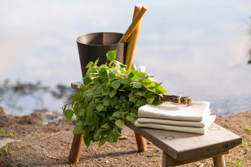 Sauna objects on wooden bench before lake at summer