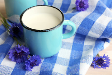 Cups of milk and cornflowers on wooden table