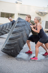 Close up of team flipping large tires outdoor