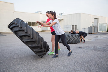 Group of people flipping heavy tires as workout