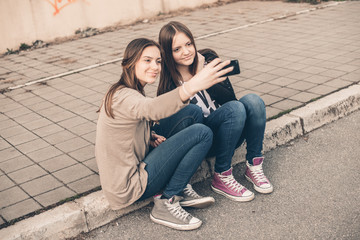 Two young girls smiling using smart phone
