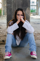 Depressed young girl sitting in the abandoned building