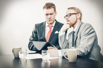 Two Men Focused on Tablet Computer