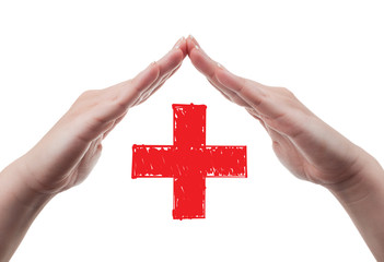 Hands protecting red cross concept