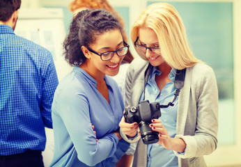 two women looking at digital camera at office