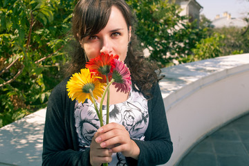 Cute female smelling bouquet of flowers outdoors