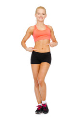 smiling sporty woman pointing at her six pack