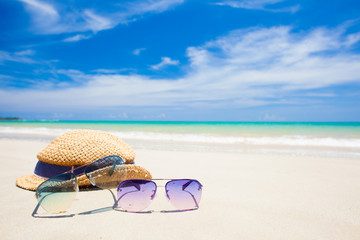 sunglasses and straw hat on tropical beach