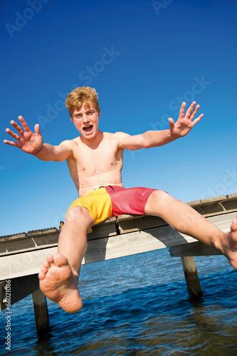 Fröhlicher Teenager sitzt auf Steg
