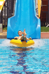 Men go down from water slide to swimming pool in aqua park.