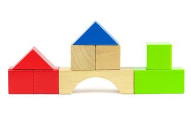 Houses made from toy wooden colorful building blocks on a white