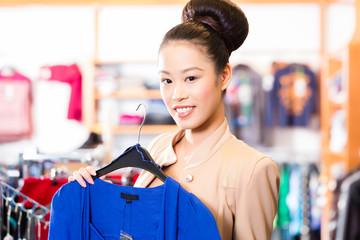 Frau wählt Kleidung in Laden beim Einkaufen