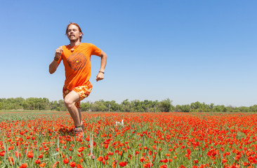 Man running on blooming poppies field