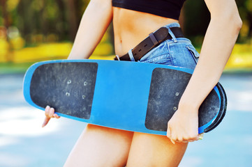Fashion portrait of female hands holding a skateboard - closeup