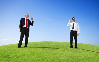 Business Men Outdoors Talking Through Tin Can Phone
