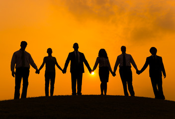Group of Business People Holding Hands in Back Lit