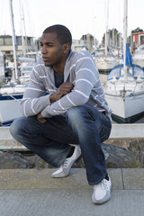 Attractive African American male model portrait squatting down a