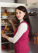 Brunette woman searching for something in refrigerator