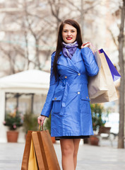 happy woman in blue cloak with shopping bags