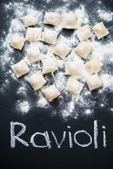 Raw italian square ravioli, above view, black wooden background