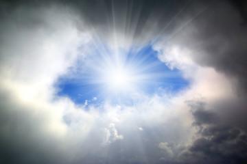 sun shining through hole in clouds