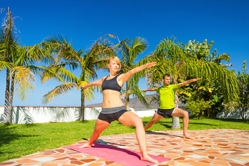 Woman and man exercise yoga outdoors