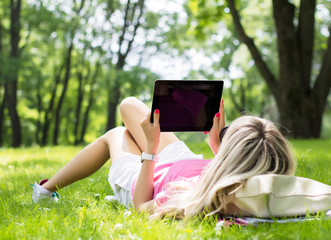 Girl using tablet computer in park