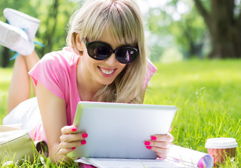 Happy young woman using digital tablet outdoors in park