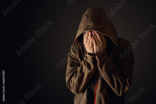 Depressive man in hooded jacket is crying