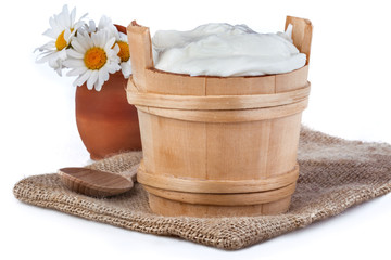 fresh yogurt in a wooden bowl with white daisies behind