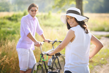 Couple with bicycles smiling toward camera