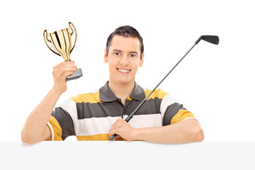Golfer holding a trophy behind a blank panel