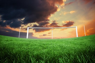 Football pitch under cloudy orange sky
