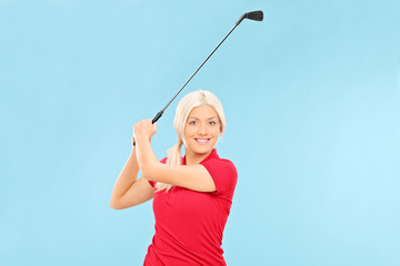 Female golfer swinging a golf club