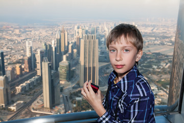 Cute boy watching at a big city from above holding a camera