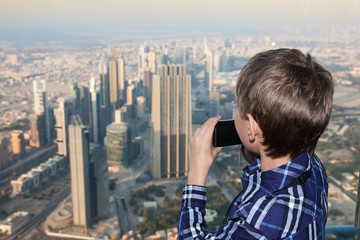Little boy watching at  big city from above holding camera