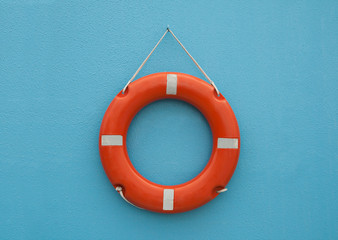 Red life buoy hanging on blue wall. Help and support concept.