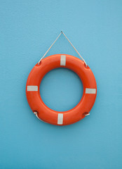 Red life buoy on blue wall. Insurance and support concept.