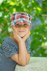 Little girl talking in plaid cap