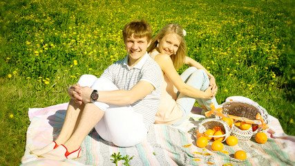 happy couple and picnic with oranges