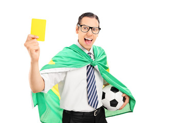 Soccer fan with Brazilian flag holding yellow card