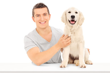 Man sitting at a table and posing with a puppy