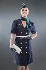 Smiling retro blonde stewardess wearing blue suit. Holding white