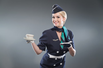 Smiling retro blonde stewardess wearing blue suit. Holding cup o