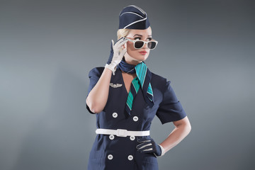 Smiling retro blonde stewardess wearing blue suit. Wearing white