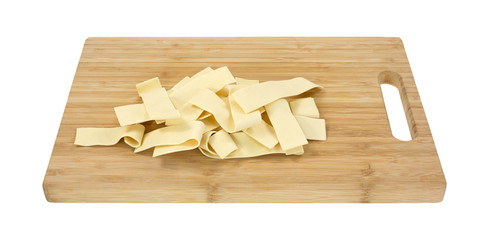 Wide egg noodles on wood cutting board
