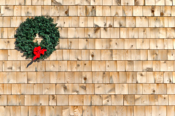 Small Christmas wreath on a cedar shingle wall